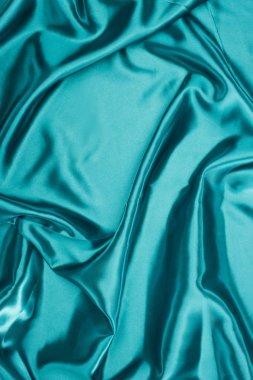 turquoise shiny wavy satin fabric background