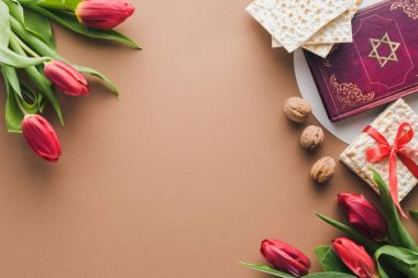 top view of traditional book with text in hebrew, bouquets of red tulips and matza on table