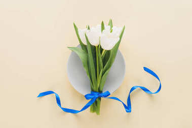 Top view of white tulips on plate isolated on beige