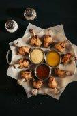 felülnézet finom sült csirke, különböző mártásokkal, a sütés papírt és fűszerek, fekete