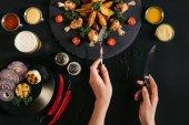 Fotografie Oříznout záběr osoby držící vidličku a nůž a jíst chutné pečené brambory pečené kuře a zelenina na černém pozadí