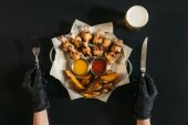 Photo cropped shot of person in gloves holding fork and knife while eating baked potatoes with sauces and roasted chicken on black