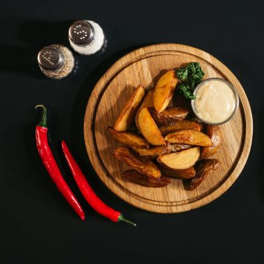 delicious baked potatoes with sauce on wooden board, spices and chili peppers on black