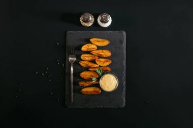 top view of tasty baked potatoes with sauce and fork on slate board and spices on black
