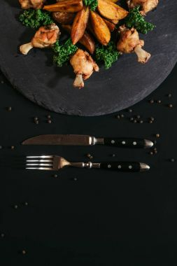 top view of tasty roasted potatoes with chicken and fork with knife on black