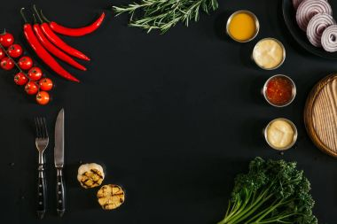 top view of various sauces, grilled garlic, fork with knife and fresh vegetables with herbs on black background
