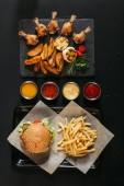 Fotografie pohled shora francouzské hranolky s vynikající burger na zásobník, různé omáčky a břidlicové desky s pečenými bramborami, grilovaná zelenina a kuřecí křídla na černém