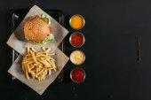 pohled shora francouzské hranolky s vynikající burger na zásobník a různé omáčky na černém pozadí