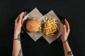 Fényképek levágott szemcsésedik-ból emberi kéz, gazdaság tálca ízletes burger és hasábburgonyával, fekete