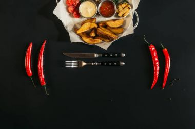 delicious baked potatoes with sauces, glass of beer, chili peppers and fork with knife on black