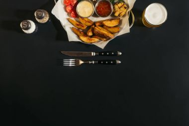top view of delicious roasted potatoes with sauces, glass of beer and fork with knife on black