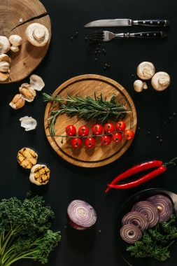 top view of fresh vegetables and herbs, grilled garlic, fork with knife and wooden boards on black