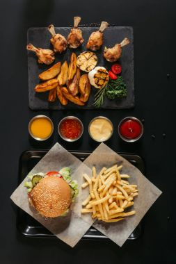 top view of french fries with delicious burger on tray, assorted sauces and slate board with roasted potatoes, grilled vegetables and chicken wings on black