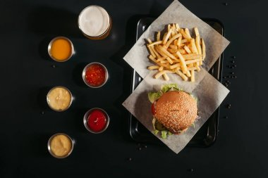 top view of french fries and tasty burger on tray, glass of beer and assorted sauces on black