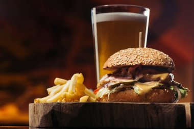 close-up view of tasty burger with turkey, french fries and glass of beer