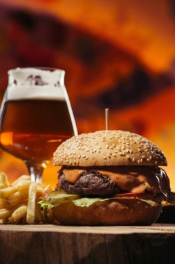 Close-up view of delicious beef burger with french fries and glass of beer stock vector