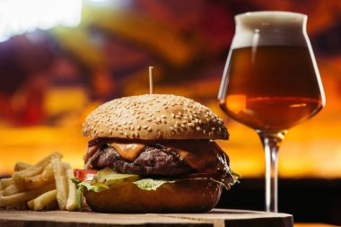tasty beef burger with french fries and glass of beer