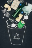 Photo various types of trash falling into drawn trash can with recycle sign on chalkboard