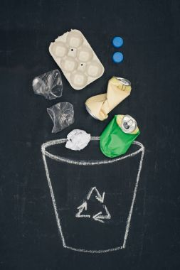 different types of trash falling into drawn trash bin with recycle sign on chalkboard