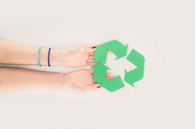 cropped shot of woman holding recycle sign on white