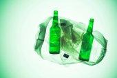 Fotografia sacchetto di plastica trasparente con varie bottiglie sotto verde tonica luce