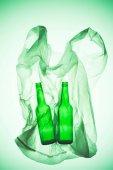 Fotografia sacchetto di plastica sgualcita con bottiglie di vetro sotto la luce verde di tonica