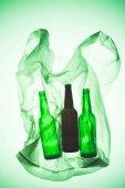 Fotografia sacchetto di plastica trasparente con bottiglie di vetro sotto verde tonica luce