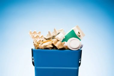 Various paper trash in trash bin on blue stock vector
