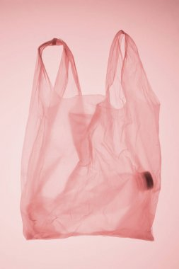 transparent plastic bag with bottle inside under pastel pink toned light