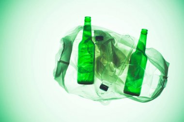 transparent plastic bag with various bottles under green toned light