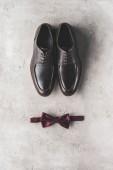 Fotografie pohled shora dvojice černé svatební boty a motýlek na šedém povrchu