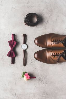 top view of wedding bow tie, boutonniere, wristwatch and shoes for groom on gray surface