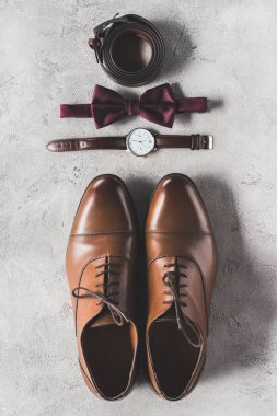 top view of pair of wedding shoes, bow tie and wristwatch on gray surface