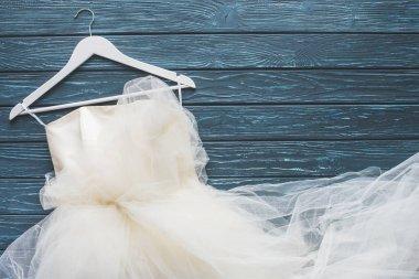 top view of white wedding dress on hanger on wooden dark blue tabletop
