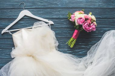 top view of wedding bouquet and white dress on wooden dark blue tabletop
