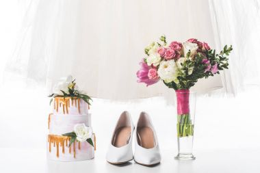 Wedding cake with shoes, dress and bouquet isolated on white stock vector