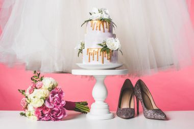 Pair of shoes, wedding bouquet, cake and white dress isolated on pink stock vector