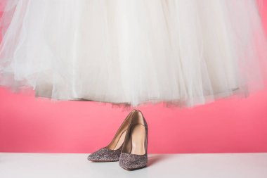 pair of shoes and wedding dress isolated on pink