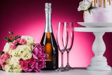 wedding bouquet, champagne and cake on stand on pink