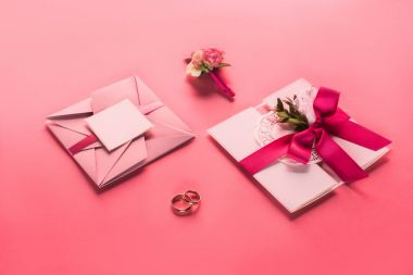 wedding rings, boutonniere and pink envelopes with invitations on pink surface