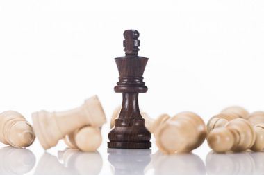 black chess king with fallen white pawns on white, business concept