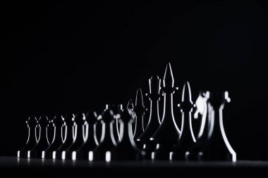 silhouettes of chess figures isolated on black, business concept