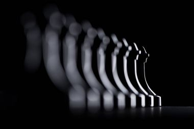 silhouettes of row of chess pawns isolated on black, business concept