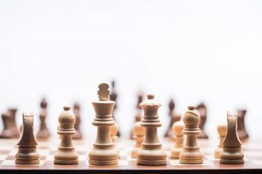 chess figures on chess board isolated on white, business concept