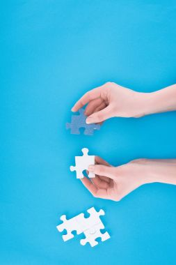 cropped image of businesswoman assembling blue and white puzzles isolated on blue, business concept
