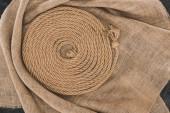 Fotografia vista superiore della corda nautica marrone disposto in cerchio su tela di sacco sulla superficie di calcestruzzo scuro