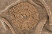 Fotografia vista superiore della corda nautica marrone disposto in cerchio su tela di sacco