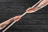 Fotografia ritagliata colpo di persone tirando la corda marina su superficie di legno scuro