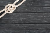 Photo top view of white nautical rope with knot on dark wooden surface