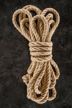 top view of tied brown nautical rope on dark concrete tabletop